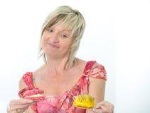 Belle femme supérieure dans la robe rose mangeant le maca jaune et rose Photographie stock libre de droits