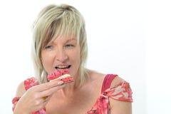 Belle femme supérieure dans la robe rose mangeant le maca jaune et rose Image libre de droits