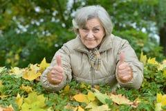 Belle femme supérieure en parc d'automne avec des pouces  Photo libre de droits