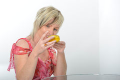 Belle femme supérieure souriant dans le macaro jaune de consommation rose de costume Photographie stock