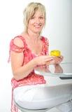 Belle femme supérieure souriant dans le macaro jaune de consommation rose de costume Photos stock