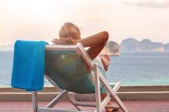 Belle femme sur l'océan de négligence de terrasse au coucher du soleil photographie stock