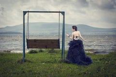 Belle femme sur la nature et l'oscillation Photo stock