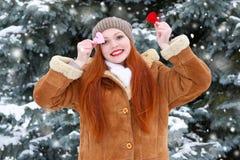 Belle femme sur la pose extérieure d'hiver avec des jouets de forme de coeur, concept de vacances, sapins neigeux dans la forêt,  Photographie stock