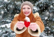 Belle femme sur la pose extérieure d'hiver avec des jouets de forme de coeur, concept de vacances, sapins neigeux dans la forêt,  Photos libres de droits