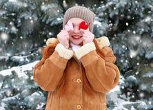 Belle femme sur la pose extérieure d'hiver avec des jouets de forme de coeur, concept de vacances, sapins neigeux dans la forêt,  Photographie stock libre de droits