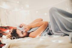 Belle femme sur le lit, intérieur de Noël, plaisir Photographie stock