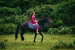 Belle femme sur un cheval Images stock