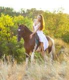 Belle femme sur un cheval Photographie stock