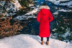 Belle femme sur une hausse dans une forêt d'hiver Photographie stock libre de droits