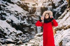 Belle femme sur une hausse dans une forêt d'hiver Photographie stock
