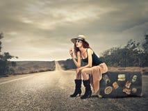 Belle femme sur une valise image stock