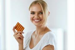 Belle femme tenant des pilules contraceptives, contraceptif oral Photo libre de droits