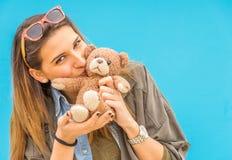 Belle femme tenant et embrassant ici le petit ours de jouet Photographie stock