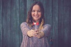 Belle femme tenant l'appui vertical de papier d'amour contre le dos en bois de mur Photo libre de droits
