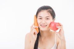 Belle femme tenant la carotte et la pomme Photographie stock