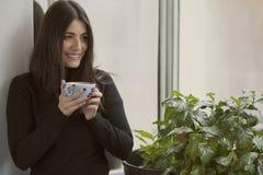 Belle femme tenant le café avec le sourire rouge de clous Image stock