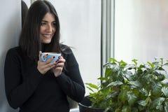 Belle femme tenant le café avec le sourire rouge de clous Photographie stock libre de droits