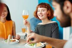 Belle femme tenant le verre tout en mangeant avec des amis Photographie stock libre de droits