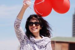 Belle femme tenant les ballons rouges Photographie stock
