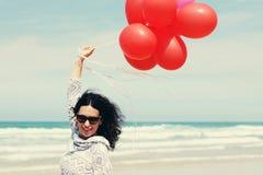 Belle femme tenant les ballons rouges Image libre de droits