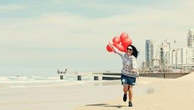 Belle femme tenant les ballons rouges Photo stock