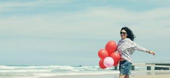 Belle femme tenant les ballons rouges Images stock