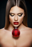 Belle femme tenant un ornement de Noël avec des dents au-dessus de fond foncé Image stock