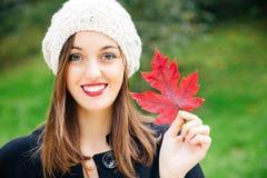 Belle femme tenant une feuille d'automne Images libres de droits