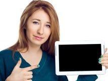 Belle femme tenant une tablette et montrant sur l'écran noir sur le fond blanc Images stock