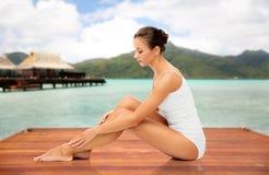 Belle femme touchant sa peau lisse de jambe image stock
