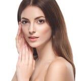 Belle femme touchant son visage par le portrait haut étroit de paumes d'isolement sur le blanc Images stock