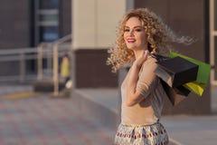 Belle femme tournant autour de et souriant avec des paniers fille heureuse avec leurs achats photos libres de droits