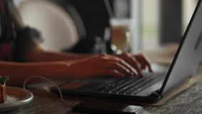 Belle femme travaillant sur son ordinateur portable sur un restaurant urbain élégant clips vidéos