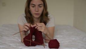 Belle femme tricotant sur un lit banque de vidéos
