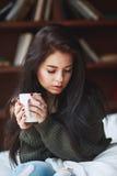 Belle femme triste de brune avec une tasse de café ou de thé Image stock