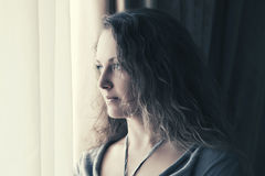 Belle femme triste regardant la fenêtre Images libres de droits