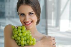 Belle femme turque tenant un groupe de raisins Images stock