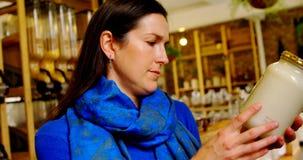 Belle femme vérifiant la bouteille de céréales dans le supermarché 4k clips vidéos