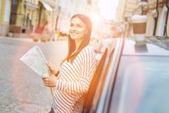 Belle femme vérifiant la carte pendant l'arrêt de voiture Photographie stock libre de droits