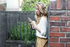 Belle femme vérifiant le téléphone dehors photos libres de droits
