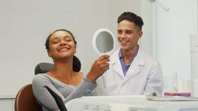 Belle femme vérifiant son sourire dans le miroir à la clinique dentaire image stock