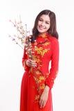 Belle femme vietnamienne avec ao rouge Dai tenant des fleurs de cerisier Image stock