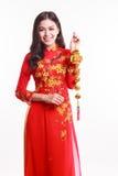 Belle femme vietnamienne avec ao rouge Dai tenant l'ornement chanceux de nouvelle année Image libre de droits