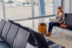 Belle fille à l'aide de l'ordinateur portable dans l'aéroport Photos libres de droits