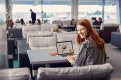 Belle fille à l'aide de l'ordinateur portable dans l'aéroport Image libre de droits