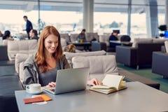 Belle fille à l'aide de l'ordinateur portable dans l'aéroport Image stock