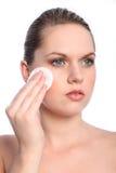 Belle fille à l'aide de la garniture de coton de produits de beauté sur le visage Photographie stock libre de droits