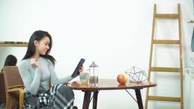 Belle fille à l'aide du comprimé et se reposant sur une chaise confortable à la maison clips vidéos