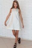 Belle fille à la mode audacieuse dans la robe blanche dans des chaussures noires à la mode posant près d'un mur de briques b Image libre de droits